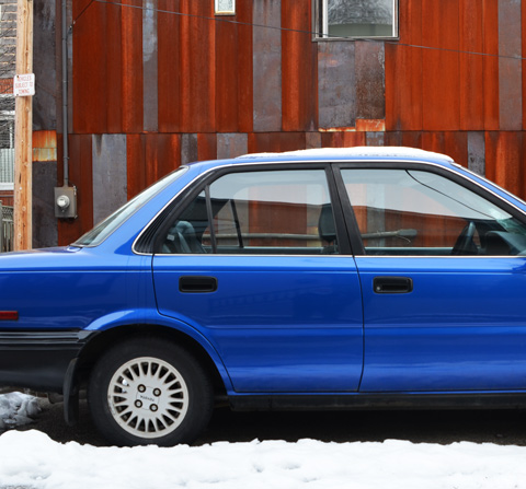 a bright blue shiny car parked in front of a rust coloured house in an alley