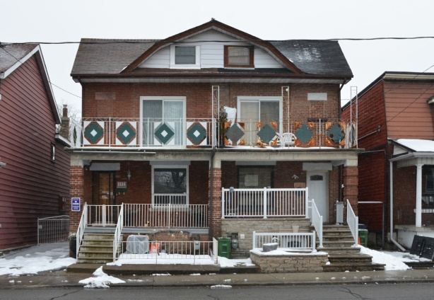 a 2 storey semi divided house on Dufferin, upper level has a balcony with with a green and white railing, winter, snow on the ground