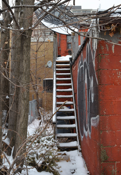 in an alley, beside an orange concrete block garage, a wooden staircase leads to an upper floor, covered with snow