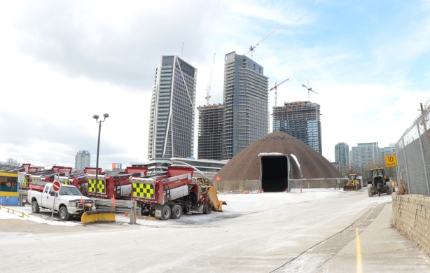 parking lot for red snowplows, city property, also a dome shaped storage for sand, condos in the background