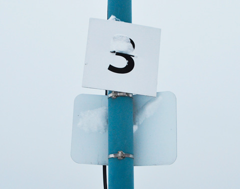 blue pole with two small signs, both with snow on them, the top sign just has the number 3 on it. the other sign has its back to the camera so it can't be read