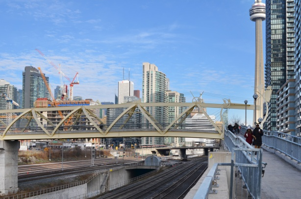 looking eastward to the puente de luz bridge and the city skyline beyond, railway tracks, cranes, new buildings,