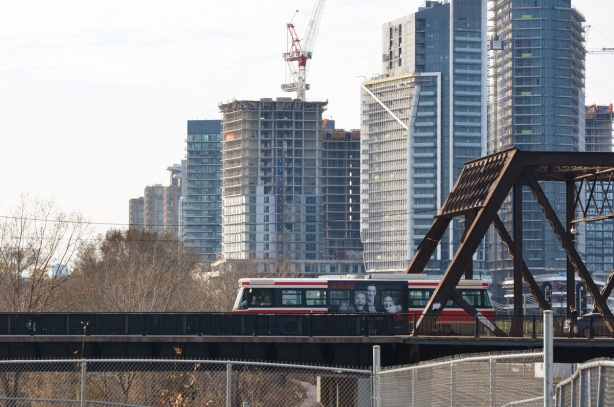 TTC streetcar passes over Bathurst street bridge over the railway tracks, new condos in the background, crane