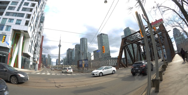 traffic at the intersection of Bathurst and Front. Brown metal bridge for Bathurst over the tracks, CN Tower and new condos in the background