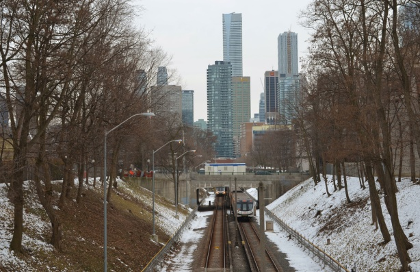 looking down the TTC subway tracks from just north of Rosedale station, highrises of downtown in the background, trees beside the tracks, 2 subway cars, one going north and the other south