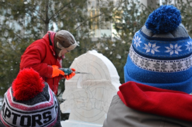 a man in a bright red winter jacket and brown hat and orange mitts is using a power drill to cut a picture of bugs bunny and the words looney tunes from a block of ice while two boys in winter toques watch