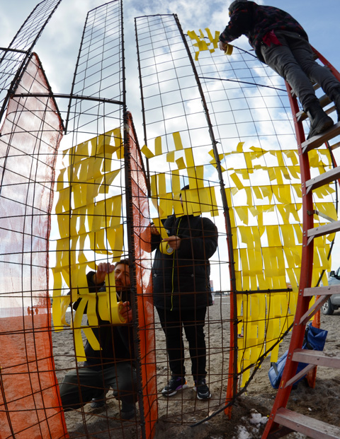 tying yellow ribbons on an orange metal frame, finishing touches on an art installation called Mirage