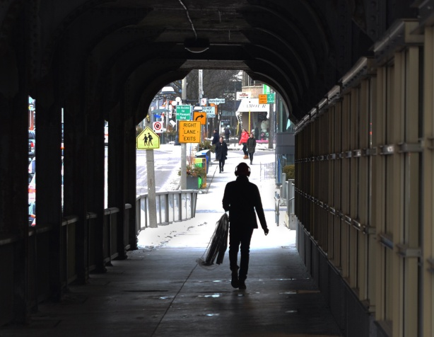 a man walks under a bridge, has headphones on and is carrying dry cleaning in a plastic cover