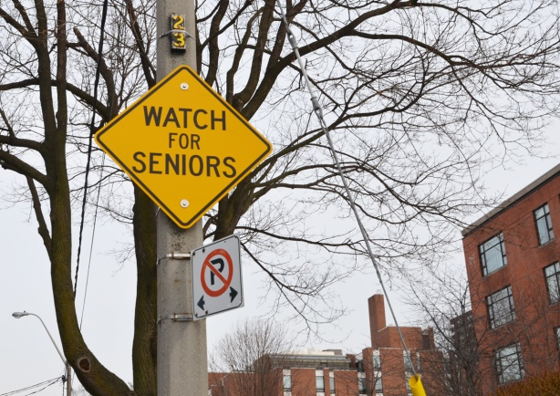 yellow traffic warning sign that says watch for seniors
