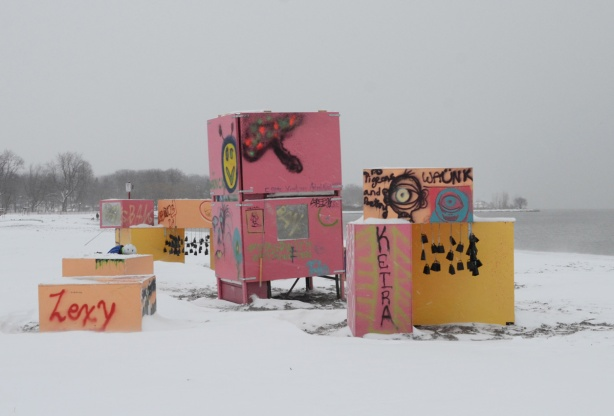 tagged and graffiti covered pink and yellow boxes stacked on the beach, art installation by Centennial College students.