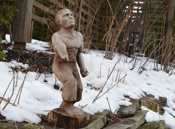 a small wooden carving of a man with a broken arm, outside in the snow