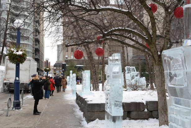 Cumberland Ave decorated for the IceFest, red balls hanging from trees, ice sculptures on display beside the sidewalk, a few people looking at them