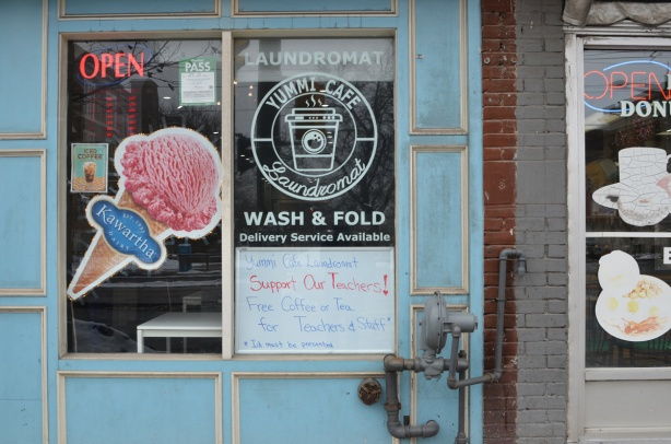 storefront, yummi cafe and laundromat, picture of pink ice cream cone as an ad for Kawartha Dairy, also a sign that says support your teachers, offering them free coffee