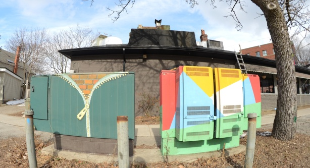 street art on two metal boxes on the sidewalk, one is a zipper opening to reveal a brick wall