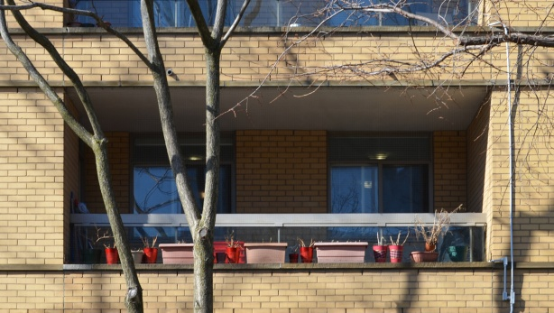 a row of pink window boxes and red planters on a balcony of a yellowish brick apartment building