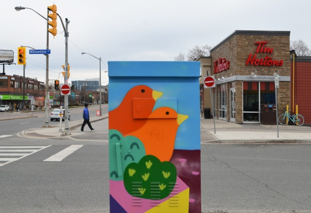 a street box painted with a red bird and an orange bird in green bushes, Tim Hortons behind as well as street scene at Willowdale and Sheppard Ave East