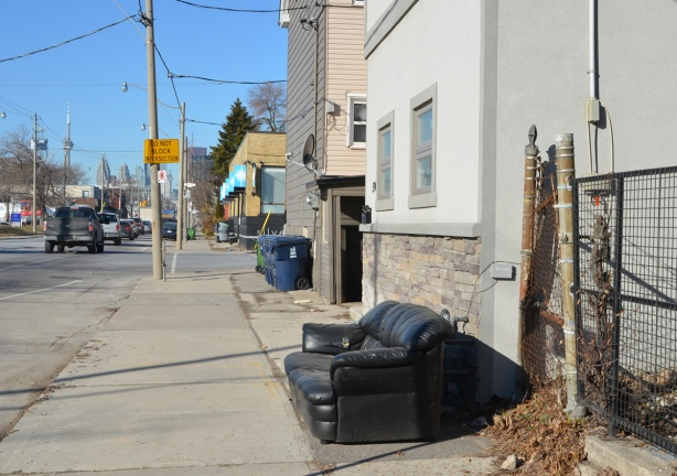 an old black vinyl couch on a sidewalk on Eastern Avenue, beside a house