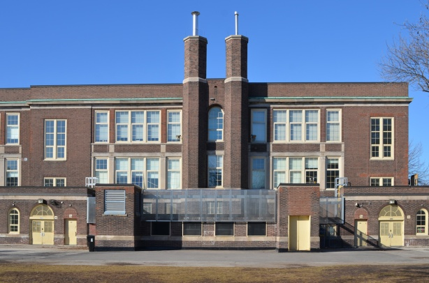 back of older brick public school, Bruce Public school with pair of chimneys and rows of windows, symmetrical.