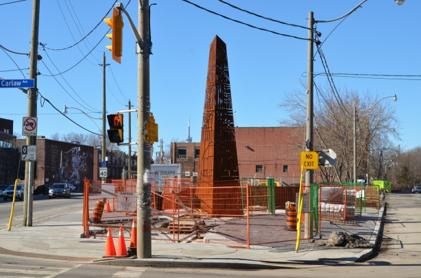 a new public art installation at Carlaw and Dundas with construction fence still around it, also a lot of utility poles around it, rusted metal cut with lasers in a design, sculpture is the shape of an obelisk