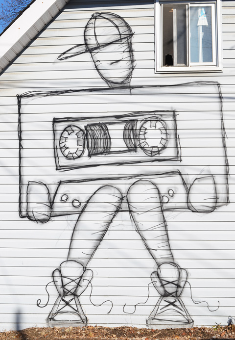 side of a white building, small window near the top, drawing of a person holding a very large cassette tape