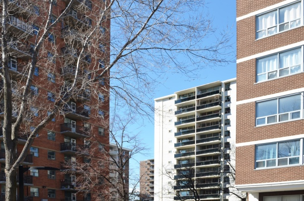 4 high rise apartment buildings in East York. winter time, trees with no leaves, blue sky,