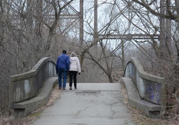 a couple walks together over a small pedestrian concrete bridge