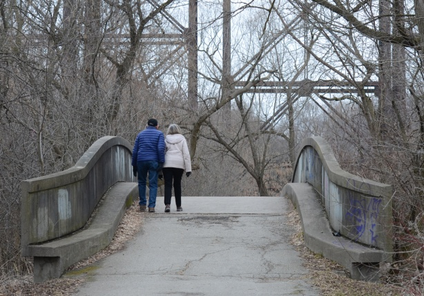a couple walks together over a small pedestrian concrete bridge
