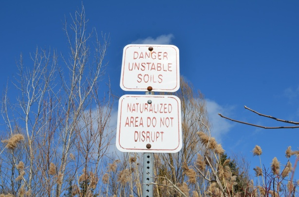 signs in a park, Scarborough bluffs, that say danger unstable soils and naturalized area do not disturb