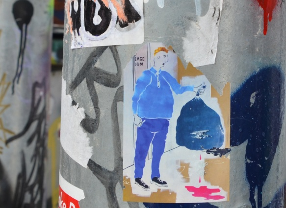daught calm sticker on a pole of a man in blue pants and sweatshirt holding up a leaking bag of garbage