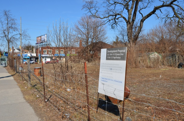 vacant lot on the corner of O'Connor and Pape, with fence around it, development proposal sign from 2014, overgrown,
