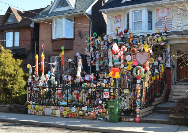 a house with a front yard full of dolls and toys, on the walls, on the fence, decorations