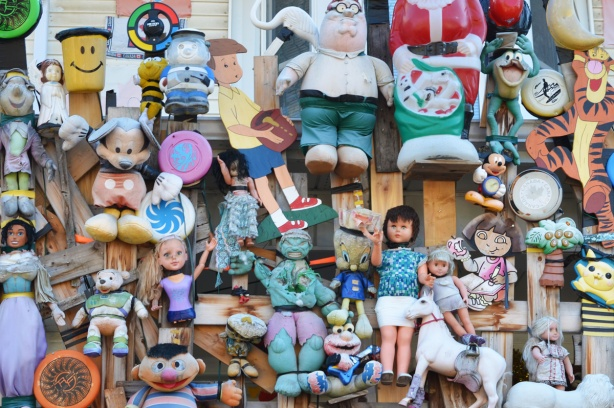 some of the dolls and toys attached to the front wall of a house