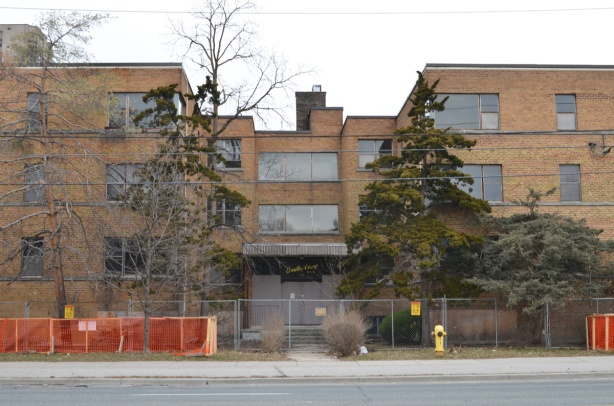 front of Dudley Court from across the street, a 1960s brick three storey apartment building, overgrown pine trees in front, also construction fence