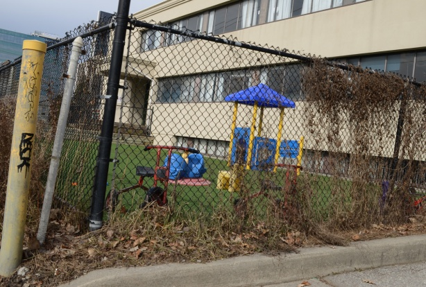 black fence around playground with some toys but no kids