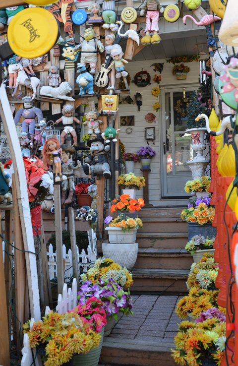 the front steps and door to the doll house - a house covered with dollas and toys, also fake plants and flowers in pots on the stairs