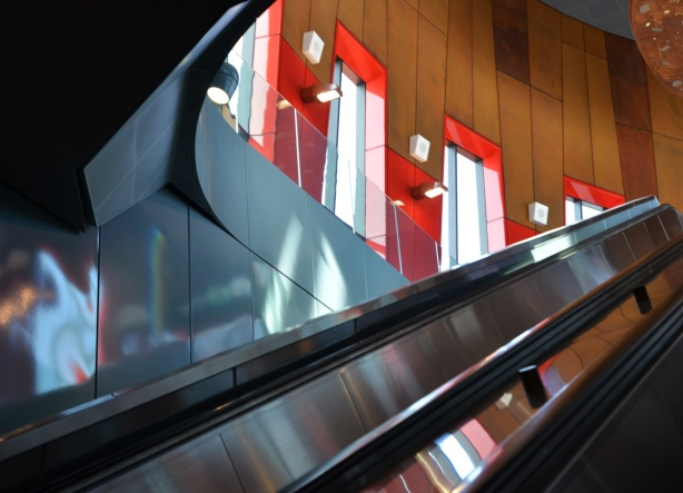 escalator and the wood wall beside it with windows with red frames, light coming in windows
