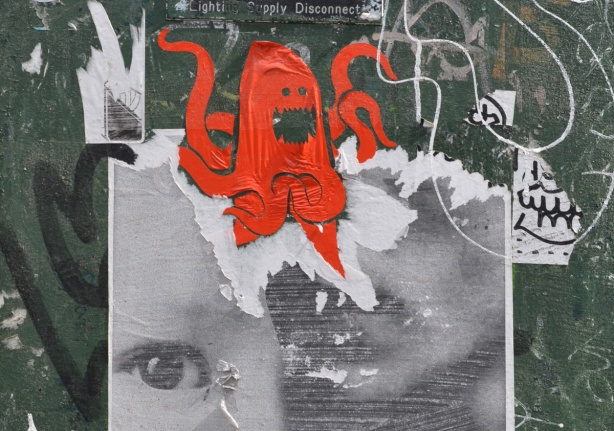 street art black and white pasteup of a face with eye still showing, torn a bit, sticker of a red octopus on top of the head