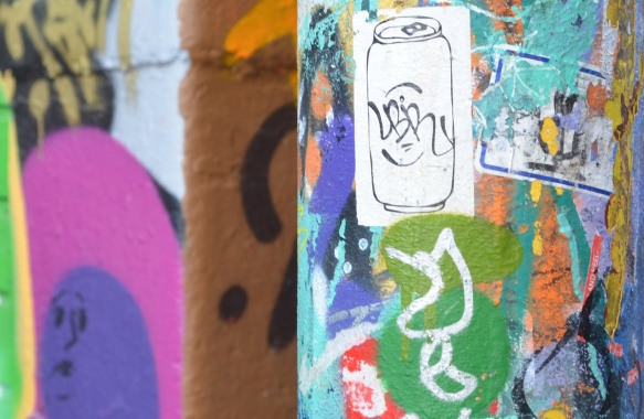 white soda can, pop can, draawing on a sticker, on a graffiti covered wall