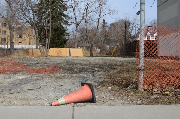 orange cone o n its side in front of a vacant lot