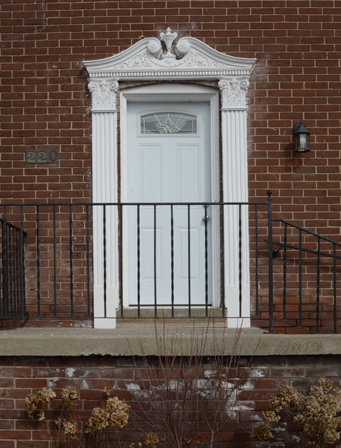 white door on small porch with black railing. door has fancy white trim with details on top