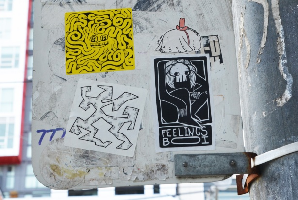 4 stickers graffiti on the back of a street sign, a yellow forge fury wiggly line sticker, a black feelings boi with white line drawing, a small white dog by sketchnate