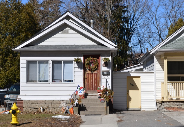 white bungalow with Christmas wreath on brown wood front door and a santa claus decoration on the front steps, a yellow fire hydrant by the sidewalk
