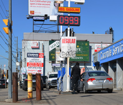 a man fills a car tank with gas at an independent gas station, sign says price of a litre of gas is 99.9 cents