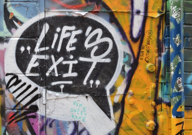 graffiti on a wall including the words Life's exit