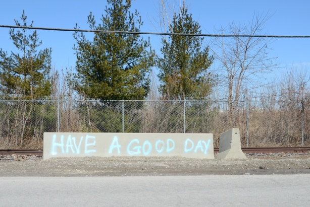 a concrete road barrier with blue spray paint words that say have a good day