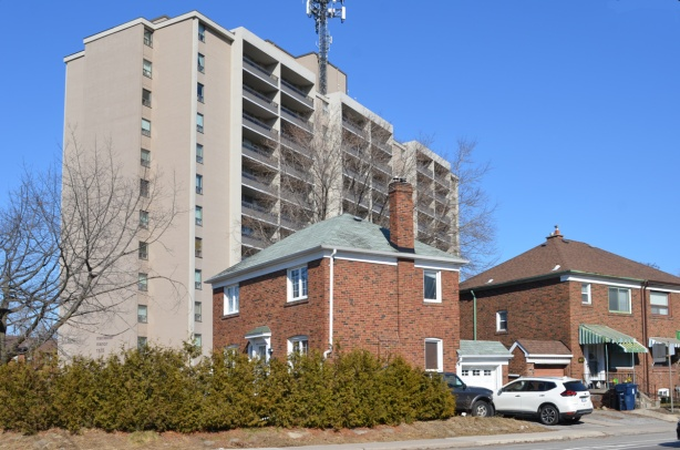 two brick houses in front of a tall apartment building