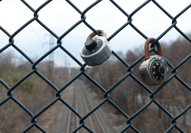 2 combination locks locked on a chainlink fence on a railway bridge