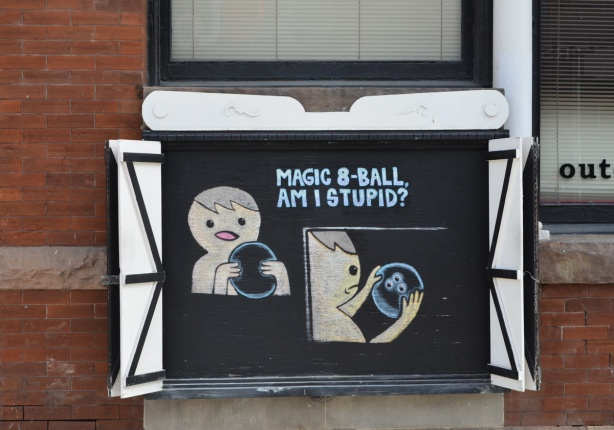 drawing on chalkboard outside, man asking magic ball am I stupid, then he realizes ball is really a bowling ball