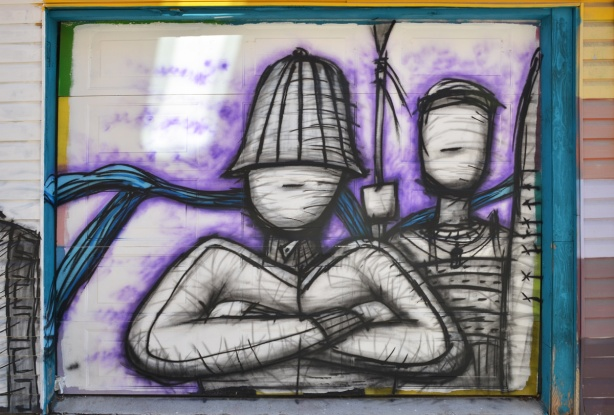 street art on garage door, faceless man with hat on and arms folded, behind hime another faceless person, all are black line drawings, with some shading.