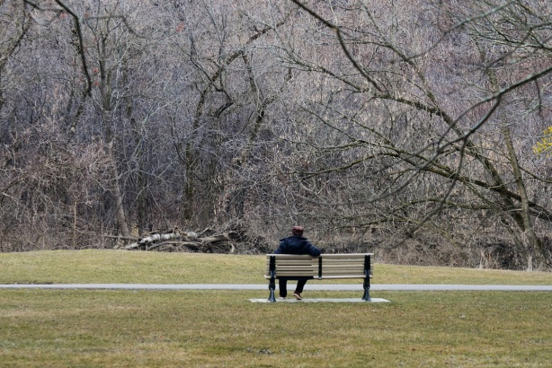 a man sitting on a bench in a park